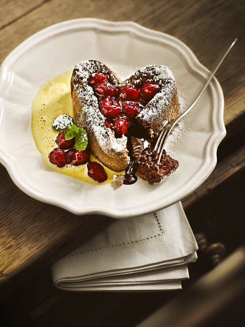 A heart-shaped chocolate cake with sour cherries on vanilla sauce