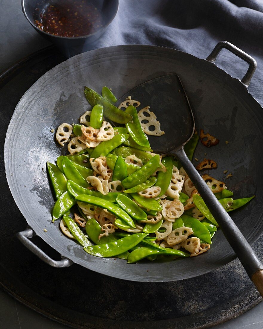Stir-fried lotus roots and mange tout in a wok