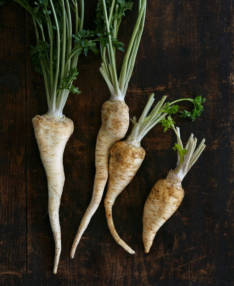 Four parsley roots on a wooden surface