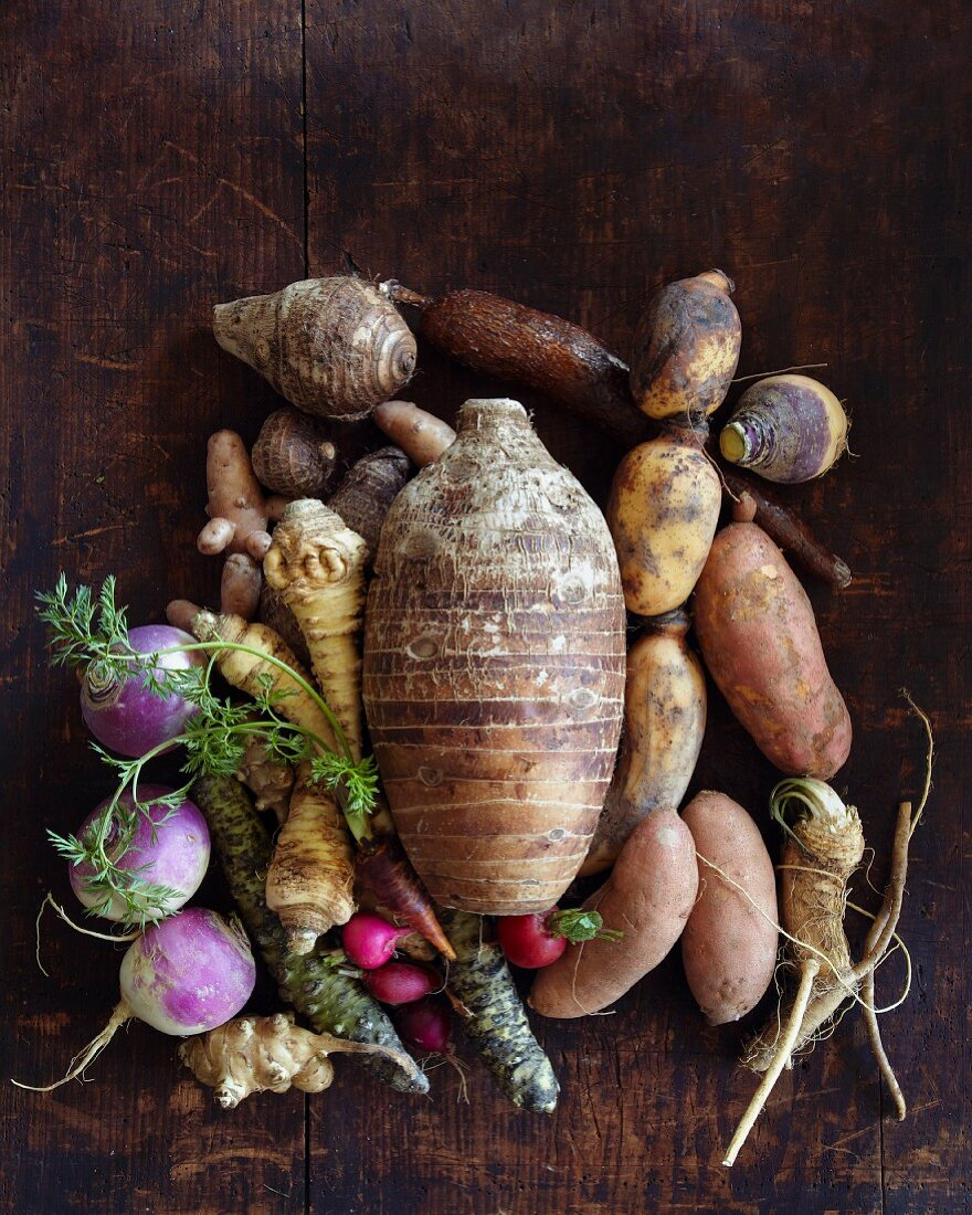 Assorted root vegetables on a wooden surface