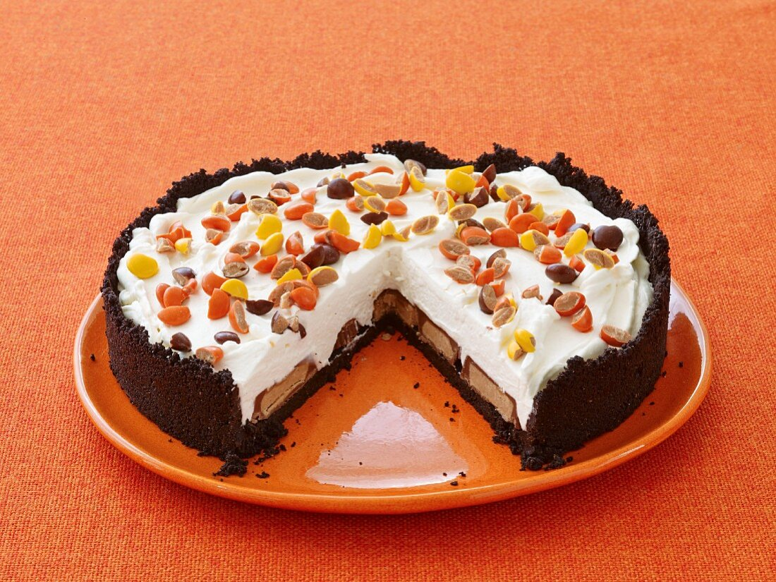 A Halloween cake filled with chocolate bars and decorated with chocolate coated peanuts