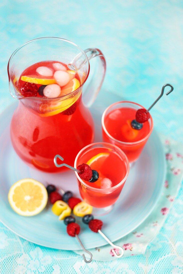 Raspberry lemonade in a glass jug and glasses