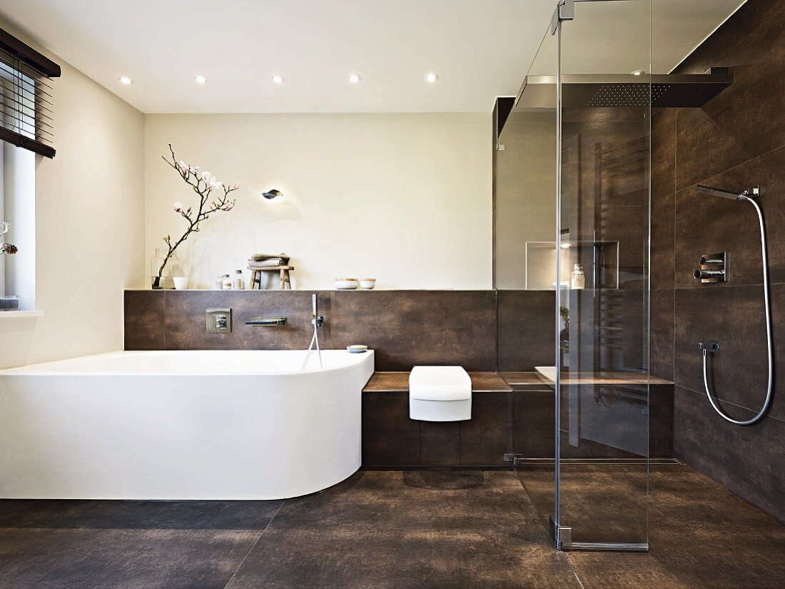 Puristisches, edles Designerbad mit weißer geschwungener Badewanne und Fliesen in Brauntönen