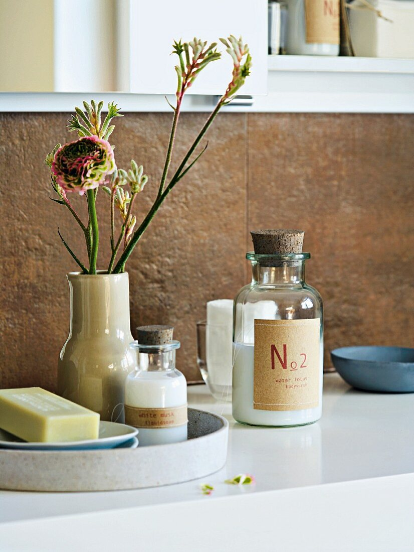 Badezubehör auf Waschtisch mit Blumen arrangiert