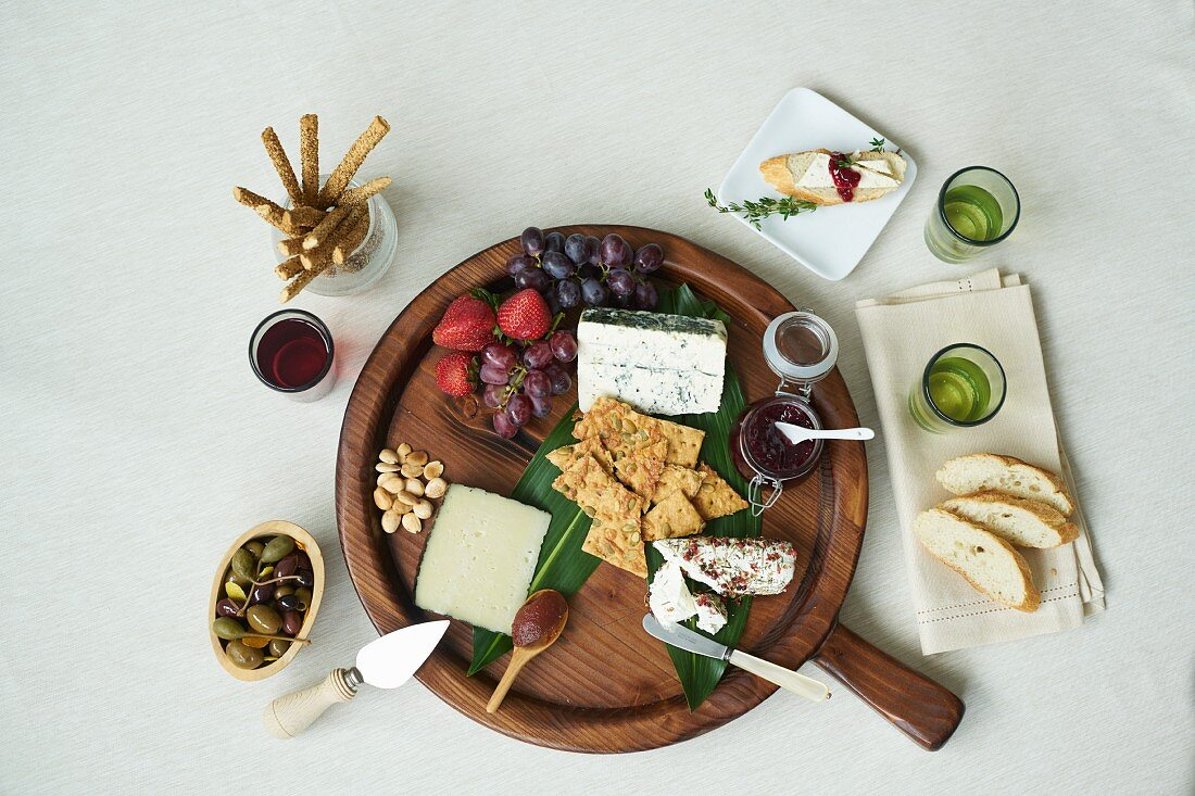 A cheesebaord with fresh fruit, sauces, nuts, capers, breadsticks, crackers and white bread