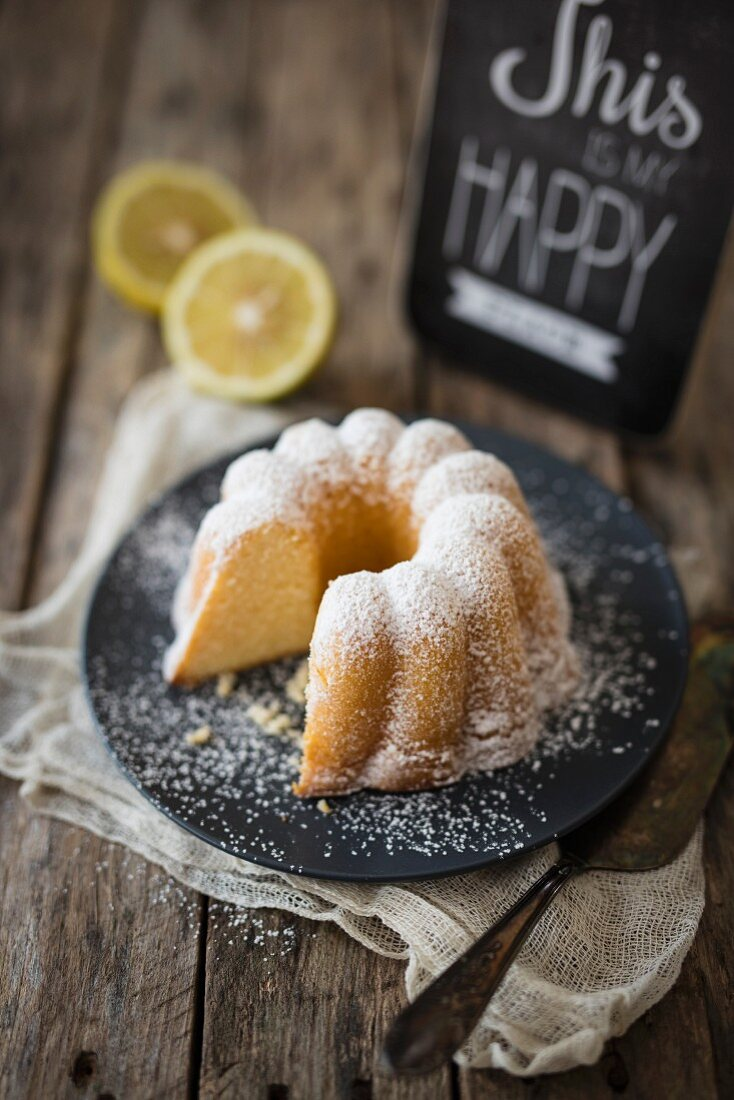 A lemon Bundt cake dusted with icing sugar on a plate