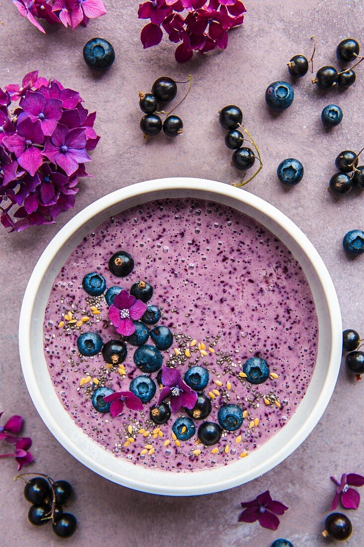 A smoothie bowl with blueberries, blackcurrants and seeds
