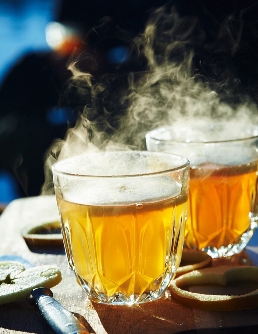 Steaming hot apple cider with heart-shaped apple slices