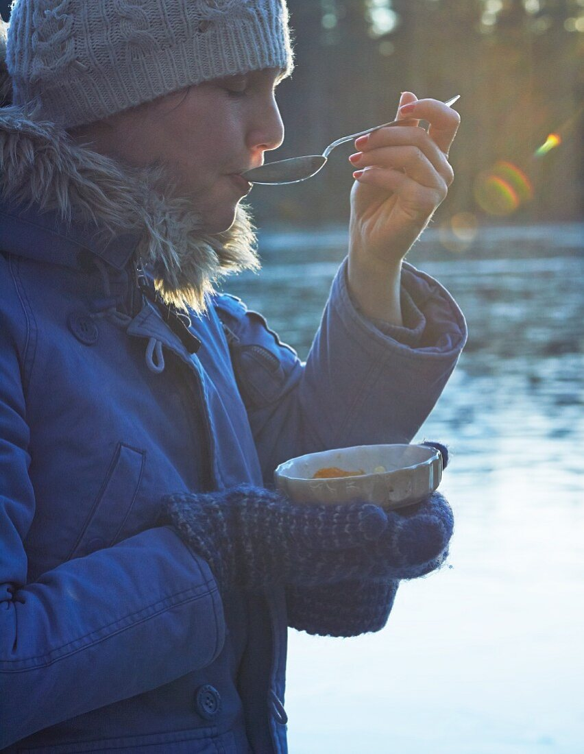 A woman dressed in warm clothing eating soup by the water