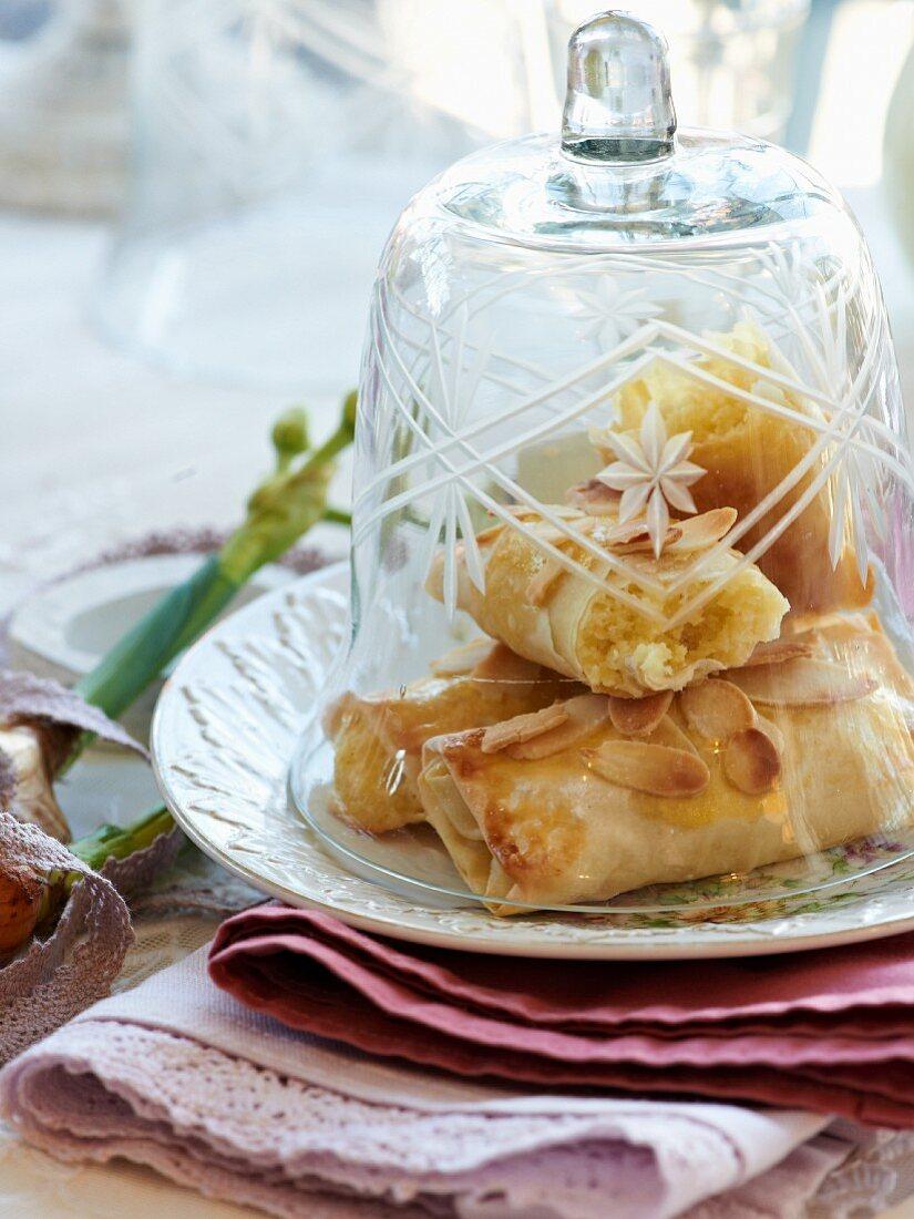 Almond filo pastries under a bell jar