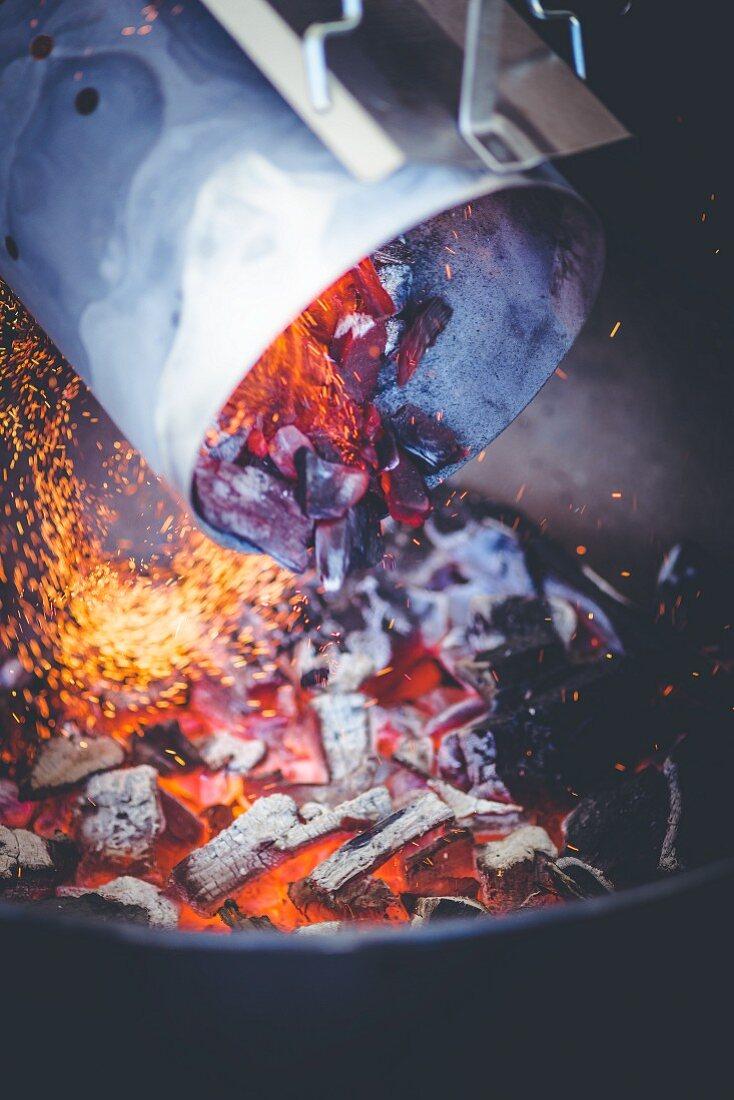 Glühende Grillkohle aus dem Anzündkamin in den Grill schütten