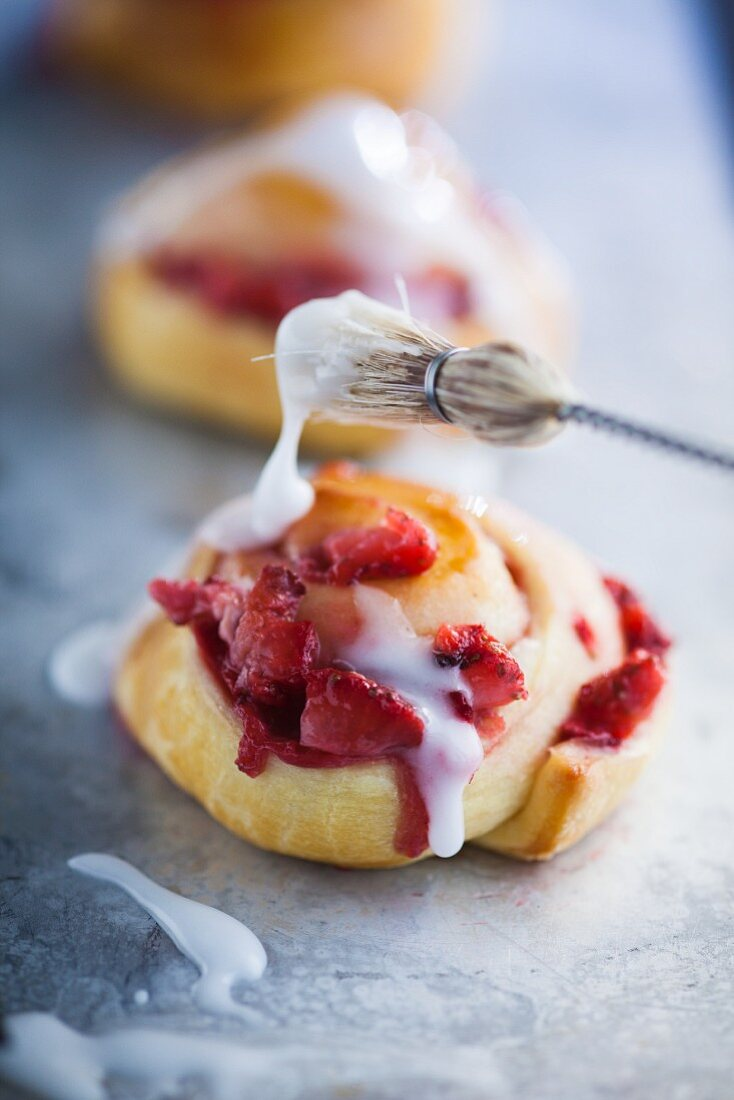 A strawberry pastry drizzled with icing