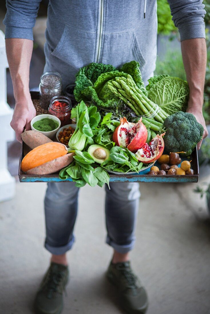 A man holding a tray of different superfood ingredients