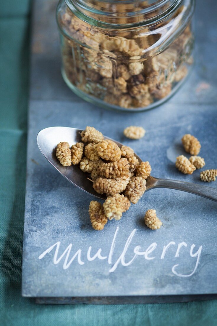Dried white mulberries in a storage jar and on a spoon