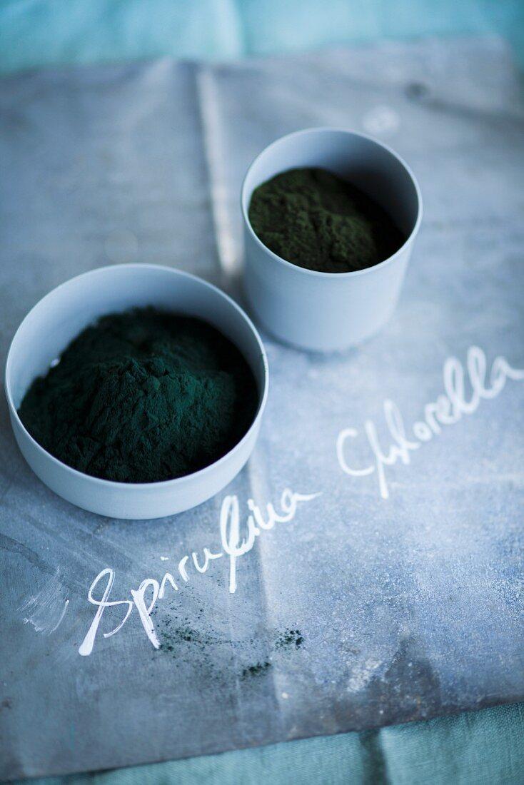Spirulina and chlorella powder in small bowls
