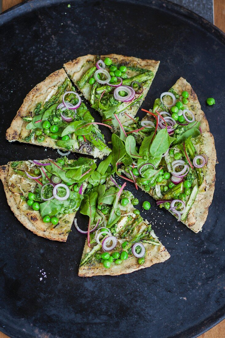 A superfood pizza with red-veined dock, peas, asparagus and pesto