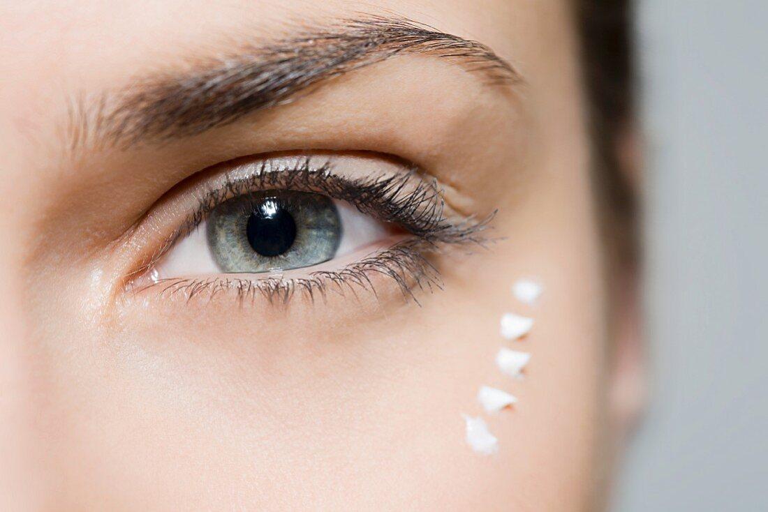 Frau mit aufgetragener Augencreme