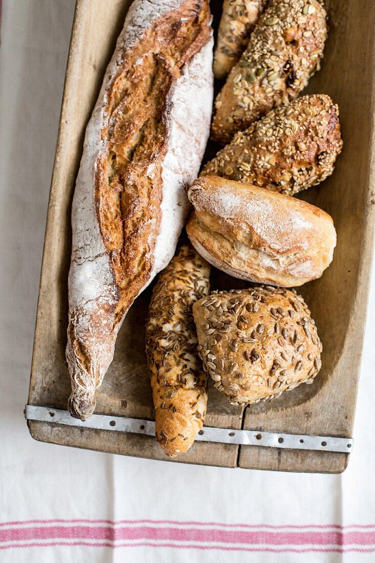 Assorted breads and bread rolls in a wooden dish