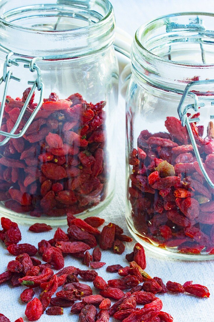 Goji berries, lose and in storage jars, on a light surface