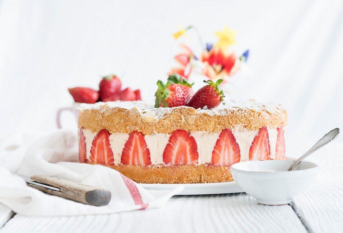 Ganze Erdbeer-Sahnetorte auf Tisch