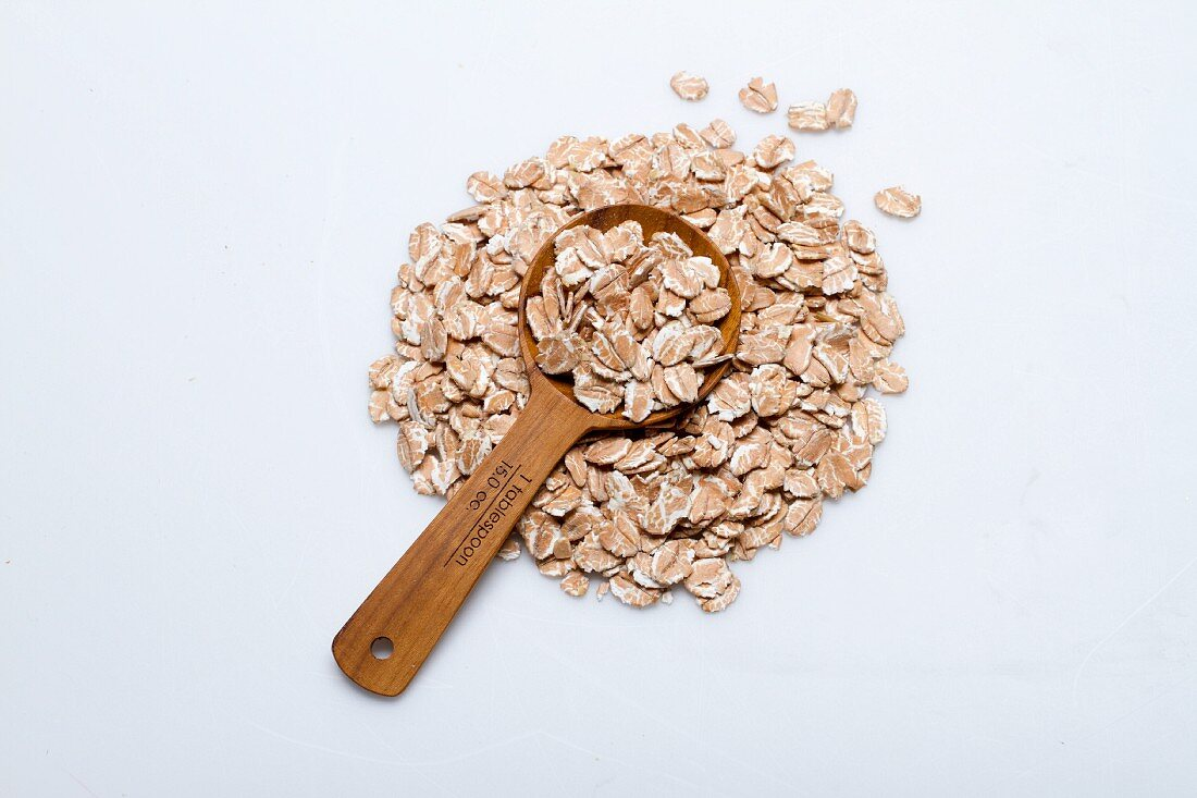 A pile of spelt flakes with a wooden spoon on a white surface