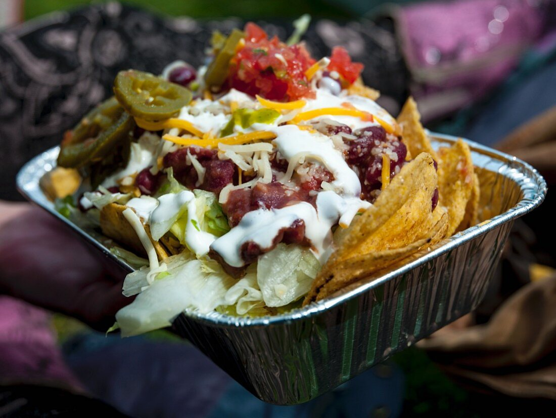 Nachos with salsa, pickled jalapenos and sour cream in an alumnium tray