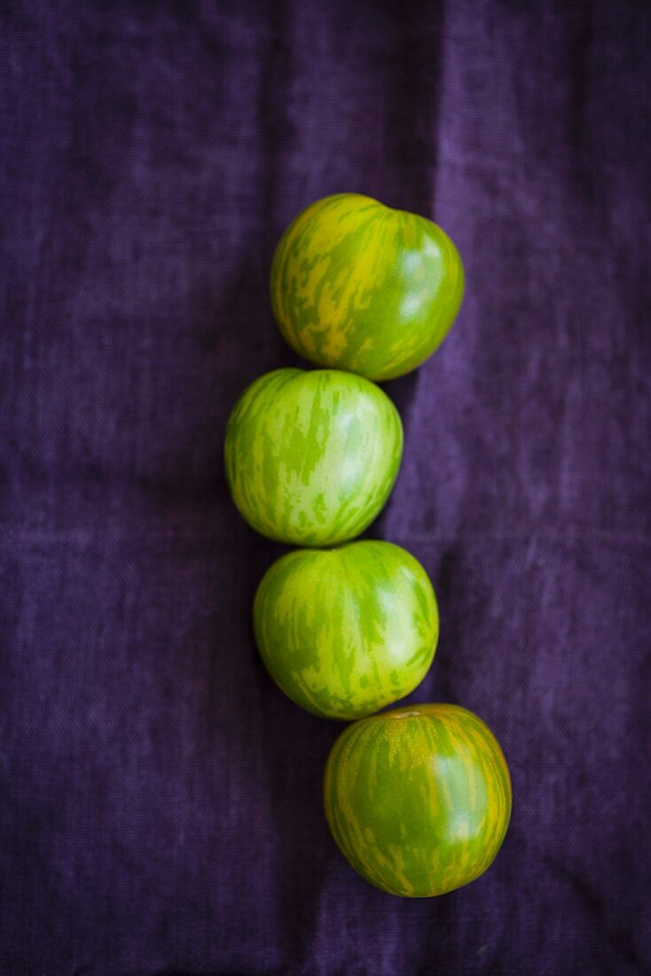 Four green zebra tomatoes on a violet cloth