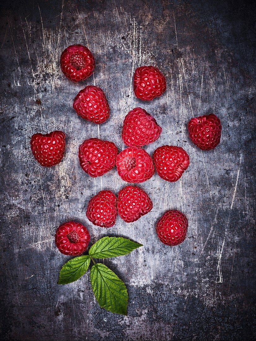 Several fresh raspberries on a grey background (seen from above)