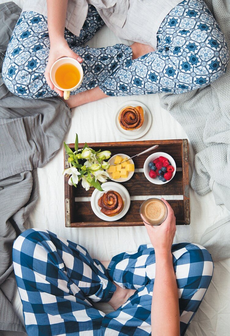 Breakfast in bed with fruit, a cinnamon swirl, coffee and tea