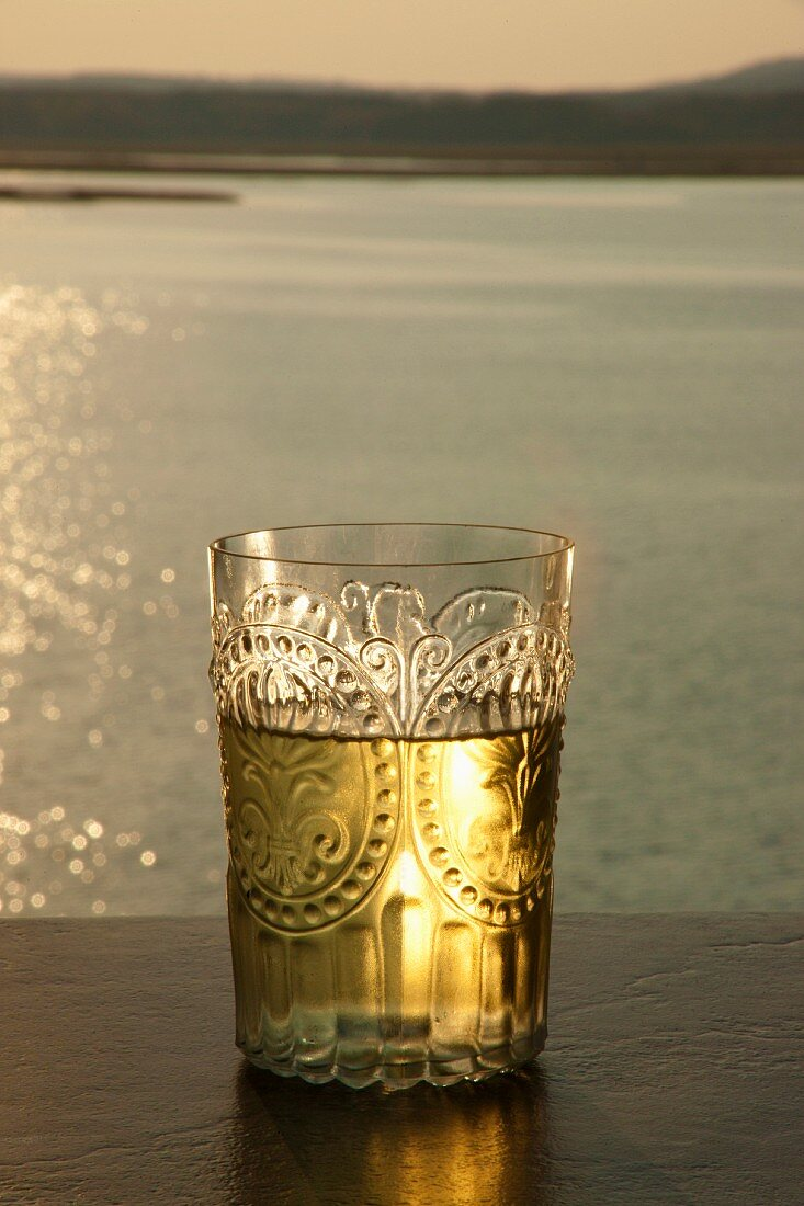 An elegant glass of white wine by the river at sunset