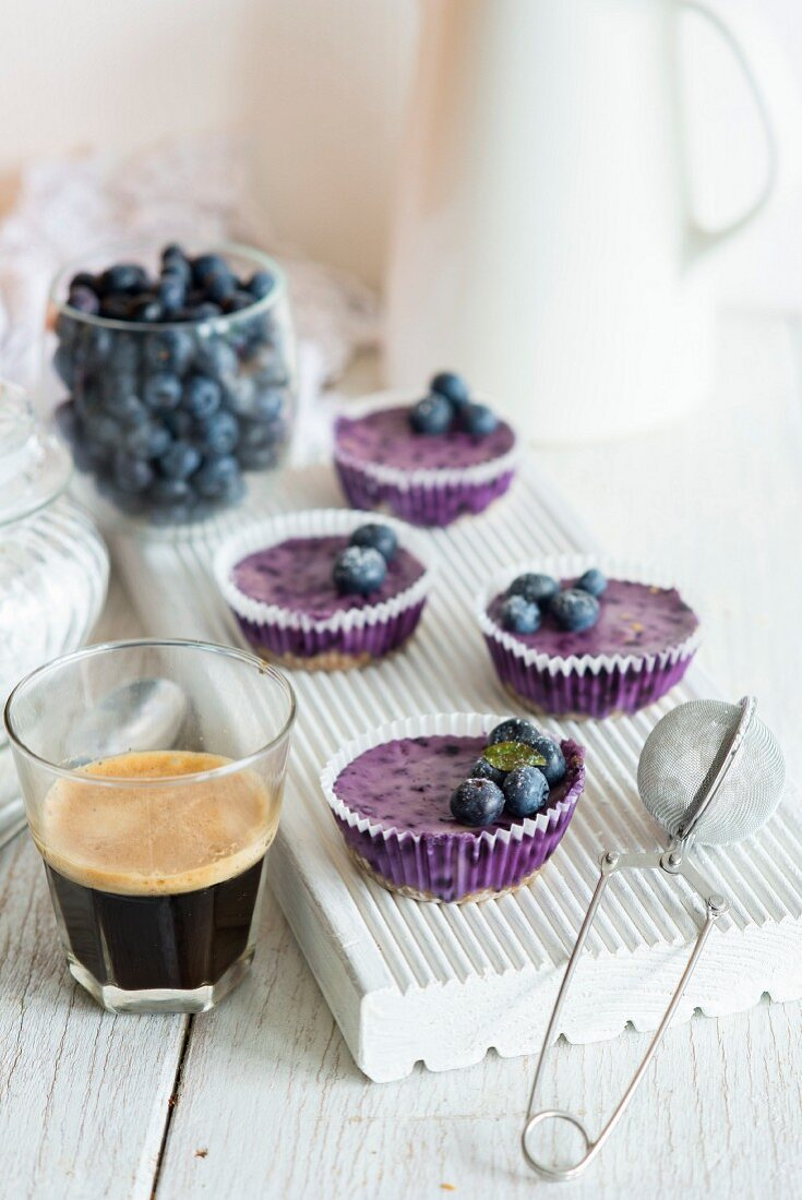 Mini blueberry cheesecakes on a white chopping board