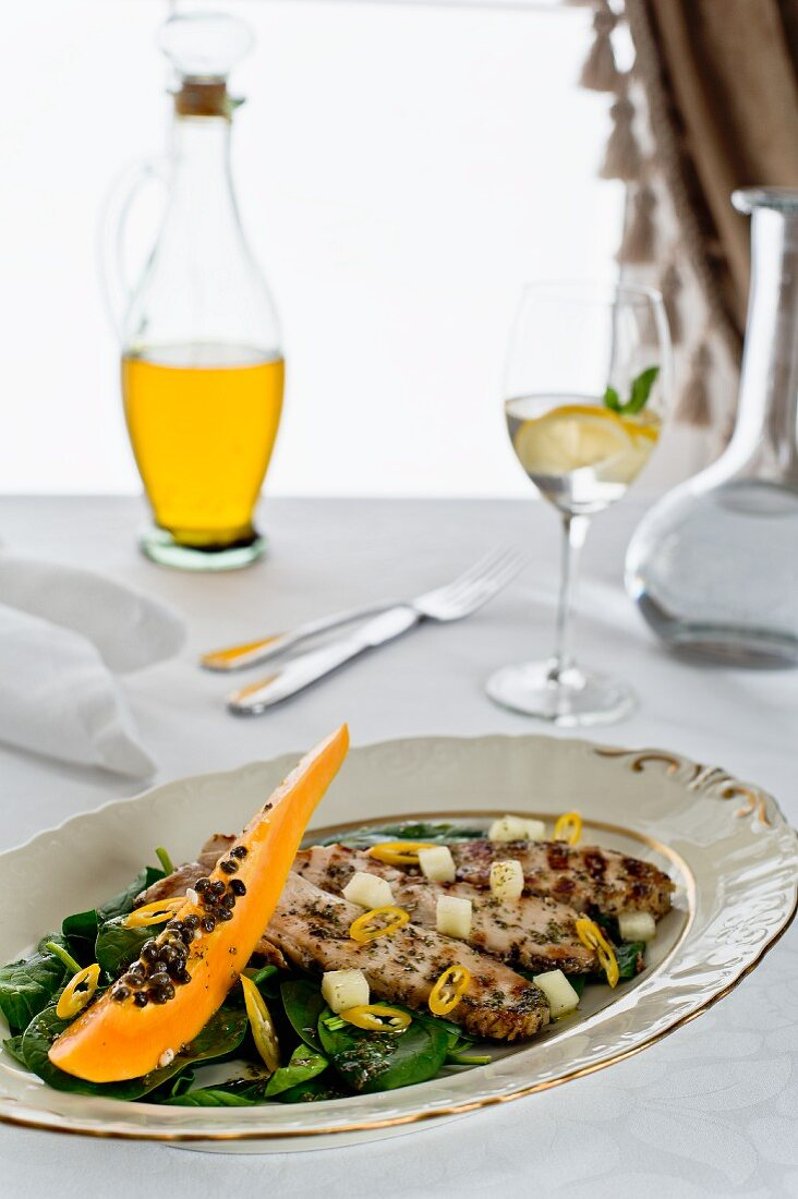 Spinach salad with mango, papaya, grilled chicken and herbs