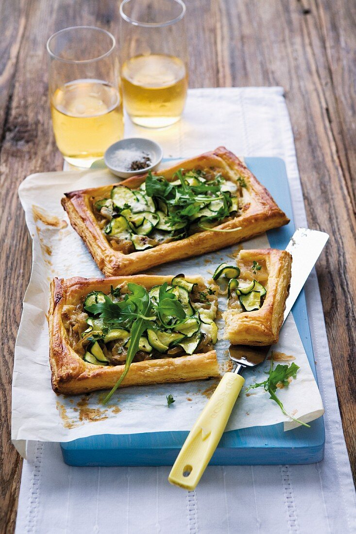 Puff pastry tarts with courgette, caramelised onion and rocket