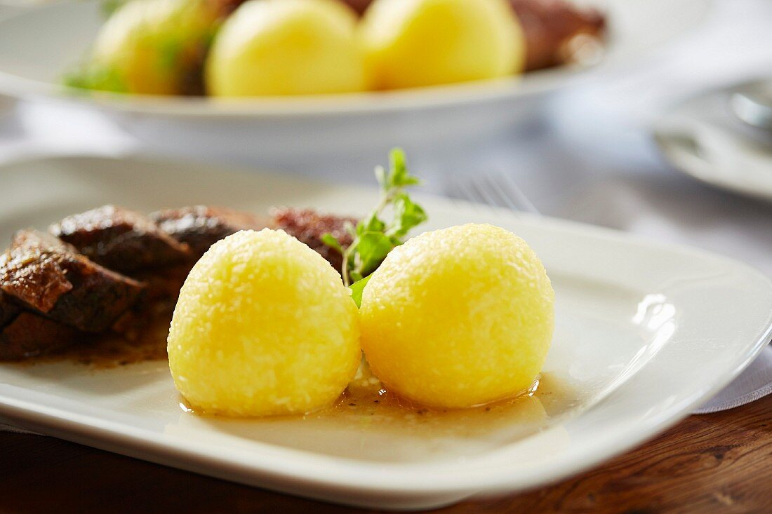 Potato dumplings as a side dish served with roast goose