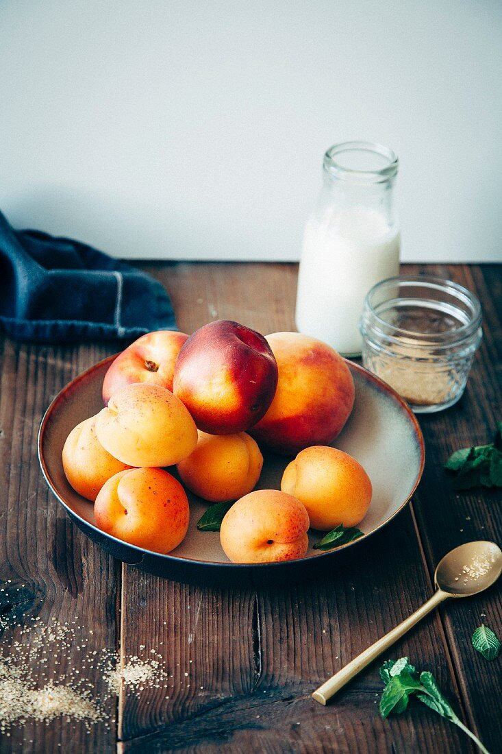 Fruits with stones (apriicots, peaches and necctarines) in a bowl with cream, brown sugar and mint