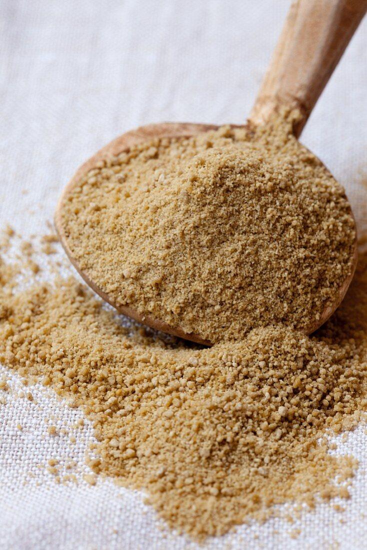 Rapadura whole cane sugar on a wooden spoon