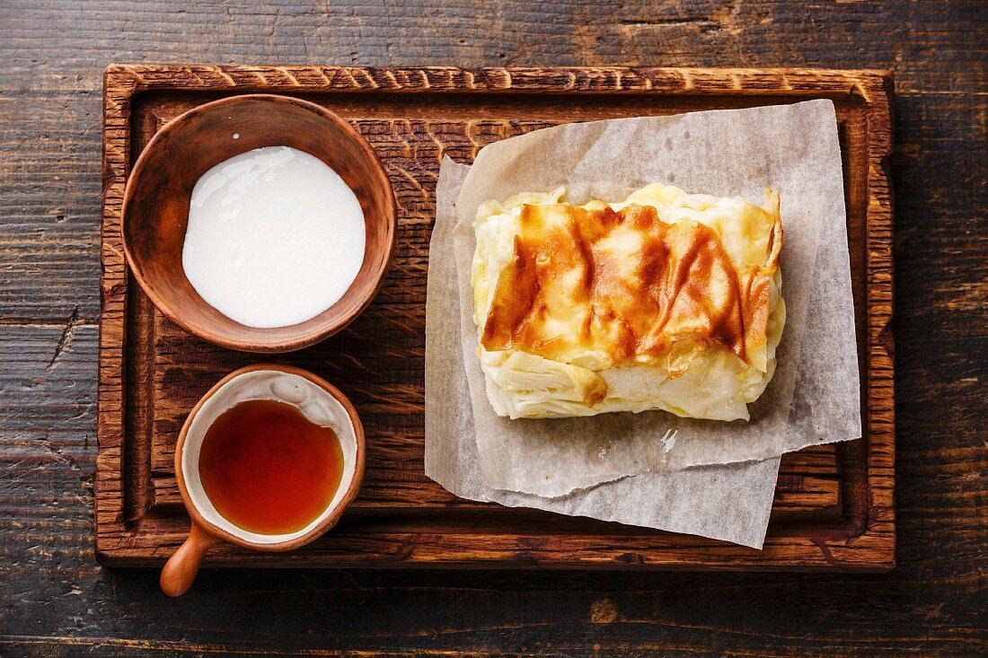 Traditional Georgian cheese layer pie Achma with creamy yoghurt sauce matsoni and honey