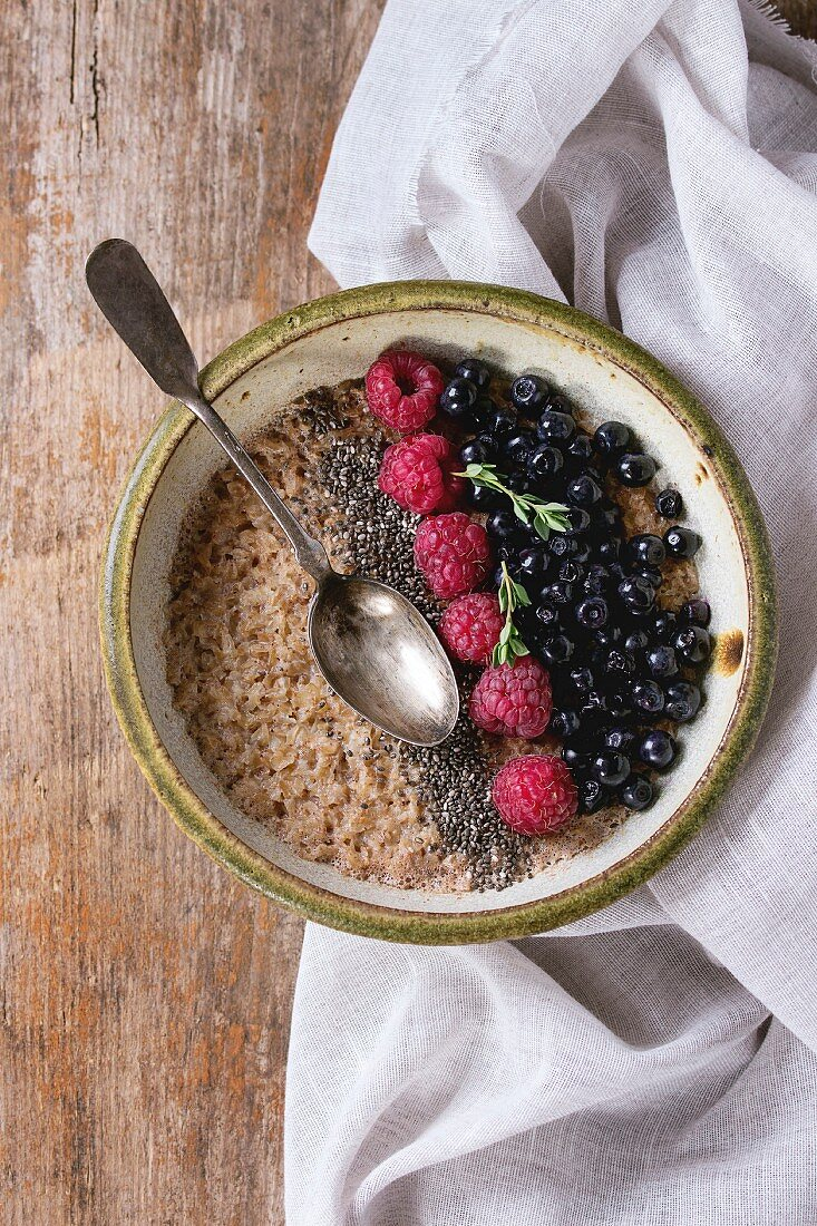 Bowl of oatmeal porridge with blueberries, raspberries and chia seeds