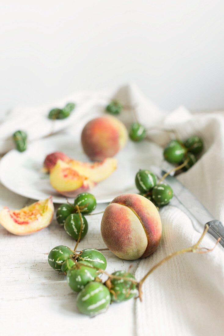 Stillleben von weißen Pfirsichen und einer Girlande von Ziergurke mit Vintageteller, Messer und altem Leinentuch