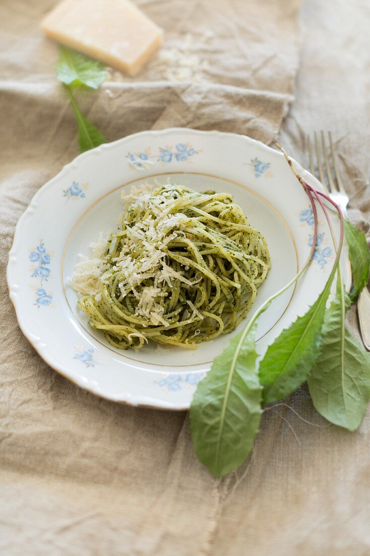 Spaghetti with home-made dandelion pesto, fresh dandelion leaves and Parmesan on a linen cloth