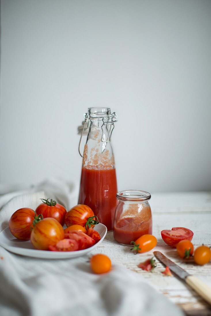 An arrangement of tomatoes (varieties: Red Zebra and Saint Orange) and fresh tomato juice in glass vessels on an old cloth