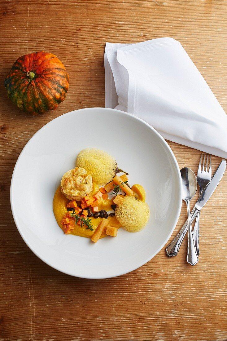 Assorted pumpkin dishes on a plate: pumpkin soufflé, pumpkin purée and pickled pumpkin