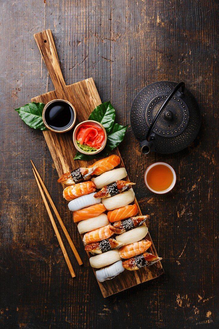 Nigiri Sushi set on wooden serving board and green tea on dark wooden background