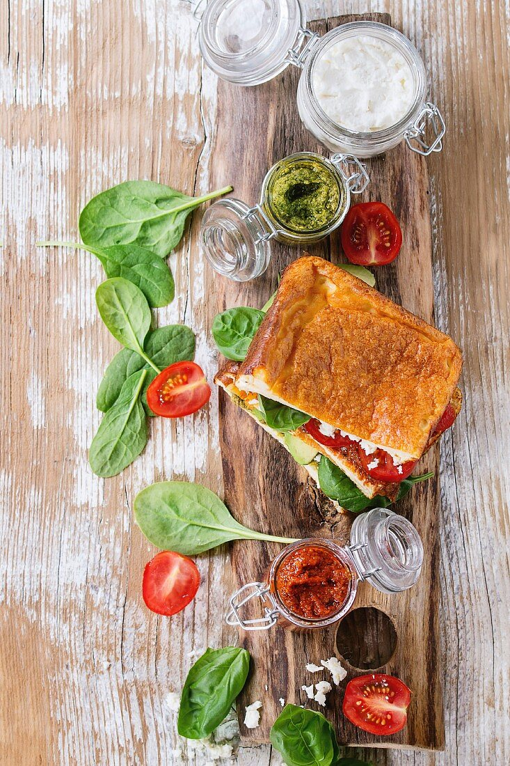 A low-carb gluten-free cloud bread sandwich with spinach, avocado, feta cheese, tomatoes and pesto