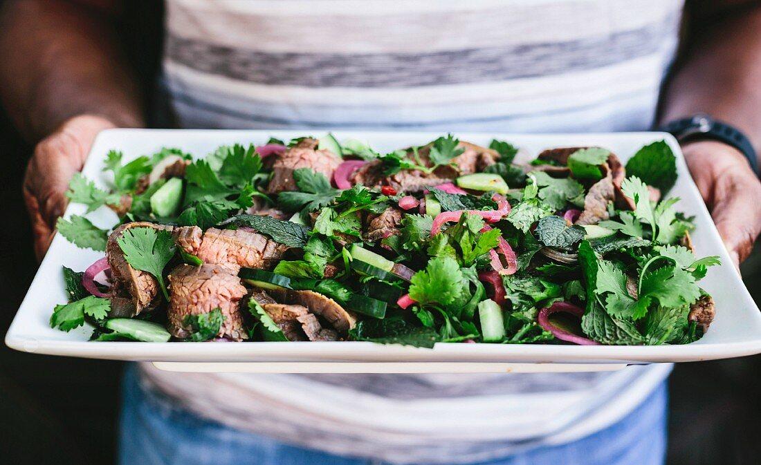 Hände halten viereckige Platte mit Thai Beef Salad