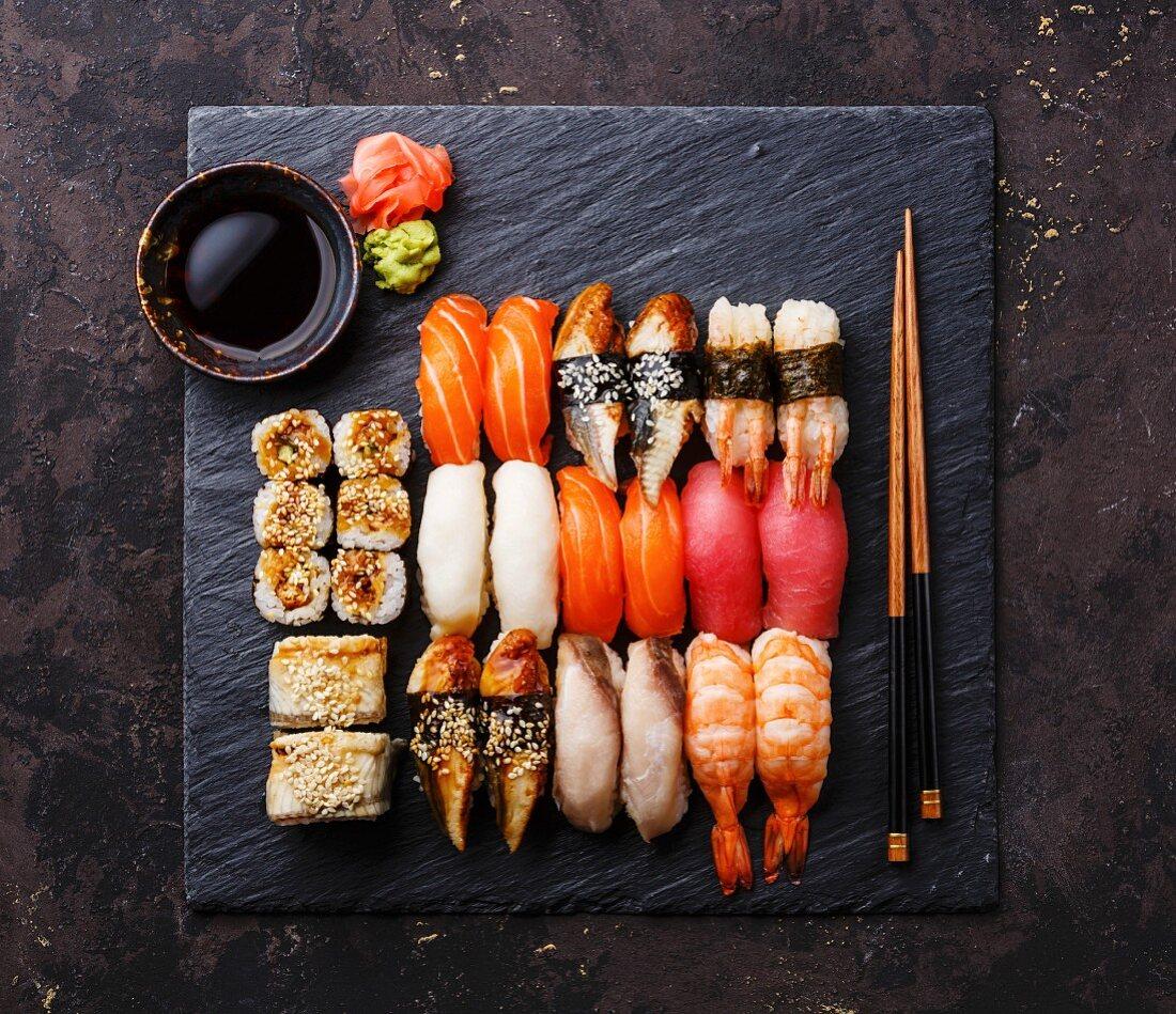 Sushi Set nigiri and sushi rolls on black stone slate plate board