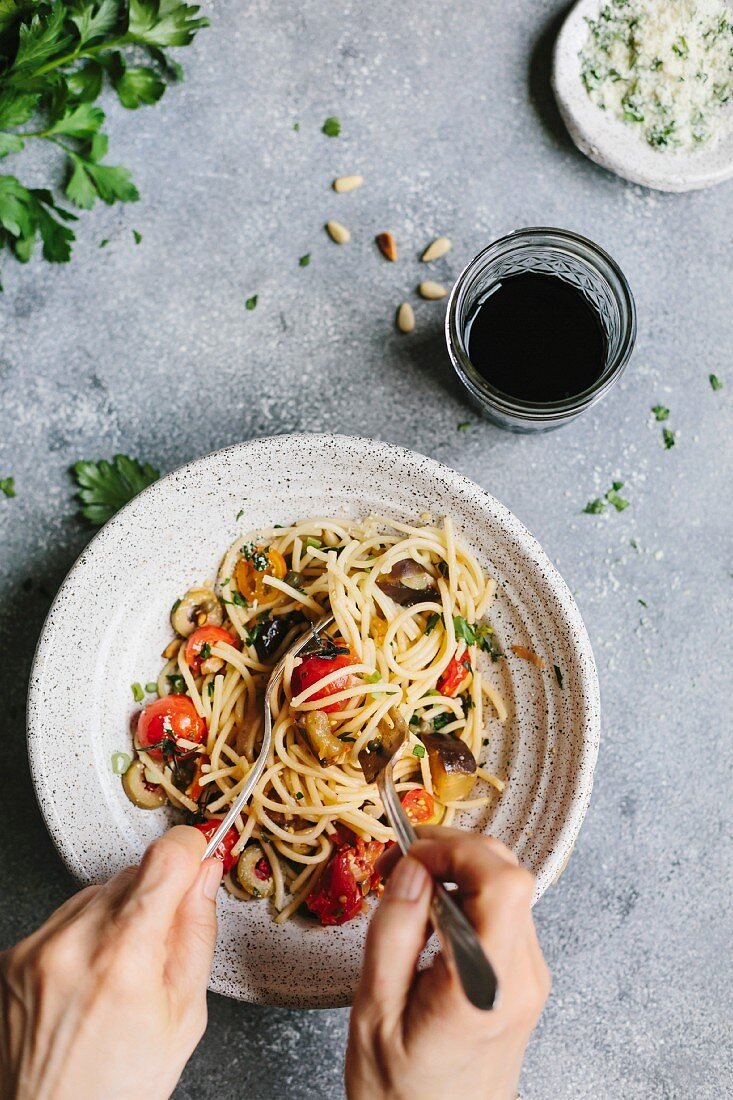 Spaghetti with aubergine and tomatoes being twirled onto a fork