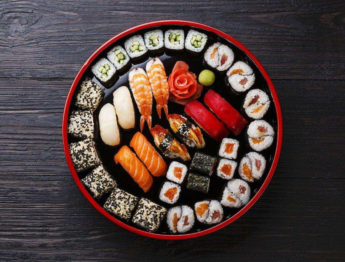 Sushi Set nigiri and rolls served in traditional Japan black Sushioke round plate