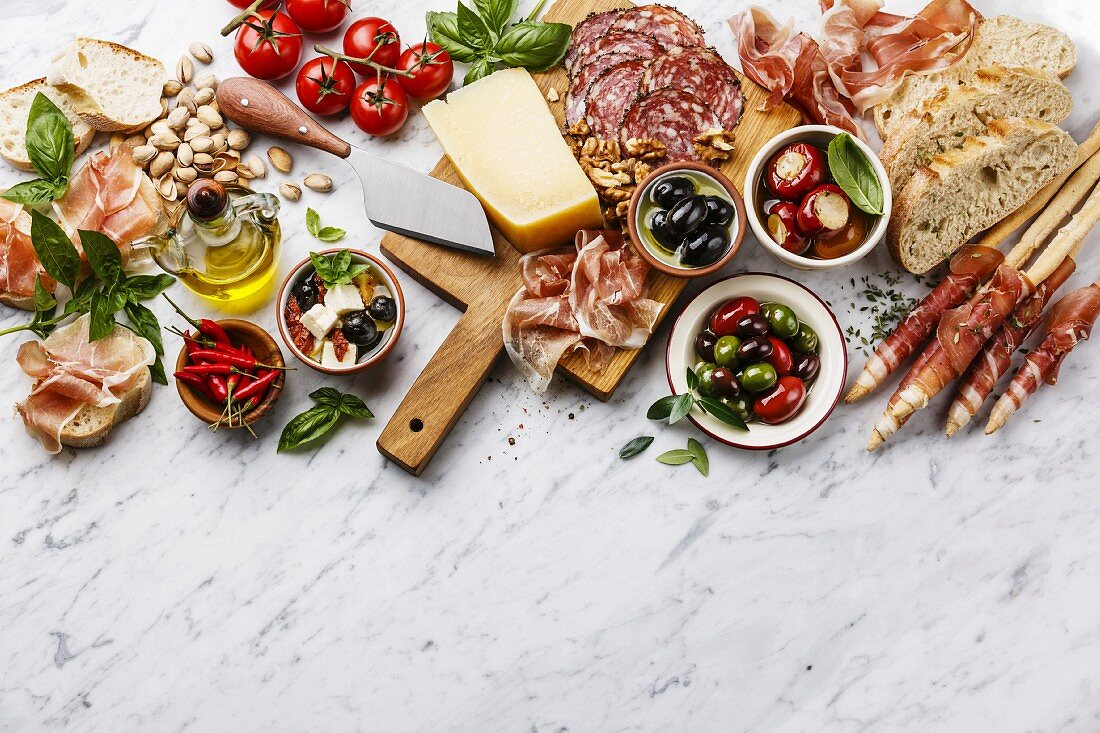 Italian snacks food with Ham, Sliced bread Ciabatta, Olives, Parmesan cheese, Grissini bread sticks, Feta cheese with dried tomatoes and Sausage