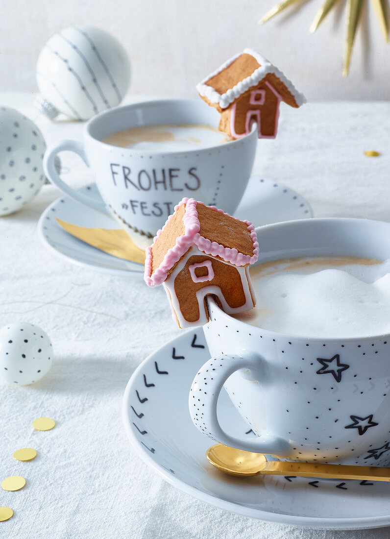 A gingerbread house on a cappuccino cup